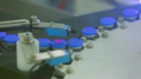 Transporte de latas estéreis da medicina em uma fábrica da medicina com verificação do laser filme