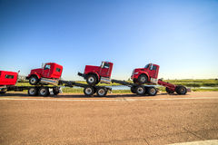 Transporte de tres nuevos camiones rojos Imagen de archivo