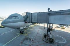 Transporte e conceito logístico pelo plano Avião com ponte do aeroporto, ponte do jato onde os passageiros conectam com o plano a fotografia de stock