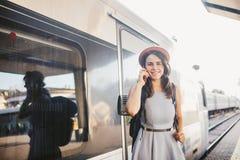 Transporte e curso do tema Mulher caucasiano nova do retrato com fundo toothy do trem do estação de caminhos de ferro da posição  fotos de stock royalty free