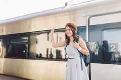 Transporte e curso do tema Retrato da mulher caucasiano nova com posição toothy do sorriso no fundo do estação de caminhos de fer fotografia de stock royalty free
