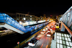 Transporte el tráfico con las luces de coches en la calle muy transitada de la ciudad urbana de la noche Foto de archivo libre de regalías