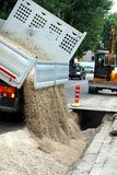 Transporte o caminhão basculante durante o esvaziamento da estrada do cascalho durante o e Fotos de Stock Royalty Free