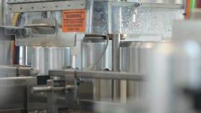 Transporte para latas de alumínio de enchimento Os bancos movem-se ao longo do transporte e a máquina fecha as tampas nas latas vídeos de arquivo
