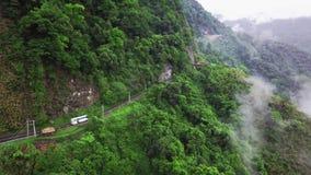 Transporte que se mueve a lo largo de enrollar a Serpentine Mountain Road curvada en parque nacional de la garganta de Taroko en  almacen de metraje de vídeo