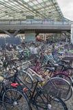 Transporte respetuoso del medio ambiente: Bicis parqueadas delante de la estación de tren, Copenhague, Dinamarca Foto de archivo libre de regalías