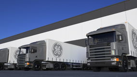 Transporte semi caminhões com carga ou descarregamento do logotipo de General Electric na doca do armazém Rendição 3D editorial Imagem de Stock
