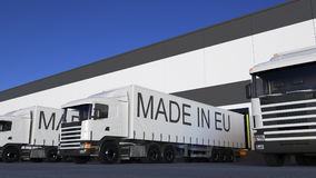 Transporte semi caminhões com FEITO no subtítulo da UE na carga ou no descarregamento do reboque Rendição do transporte 3D da car Foto de Stock