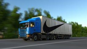Transporte semi o caminhão com a inscrição e o logotipo de Nike que conduzem ao longo da estrada de floresta Rendição 3D editoria Foto de Stock