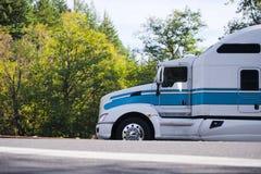 Transporte semi o perfil poderoso na estrada com árvores do outono Imagem de Stock