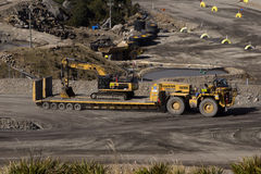 On the transporter. A 40 ton digger hitches a ride on a huge custom-built transporter at an open cast coal mine on August 31, 2013 near Westport, New Zealand royalty free stock image
