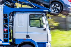 Transporter truck loaded with cars on uk motorway in fast motion.  royalty free stock photography