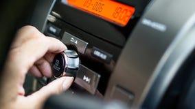 Transporter- und Autoselbstaudiokonzept - Mann, der Autoaudio- und Radiostereolithographie auf Autoplatte verwendet Lizenzfreies Stockfoto