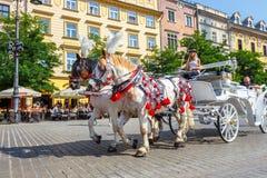Transportes do cavalo no quadrado principal em Krakow em um dia de verão, Polônia imagens de stock