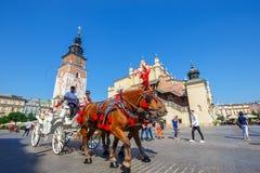 Transportes do cavalo no quadrado principal em Krakow em um dia de verão, Polônia foto de stock