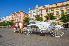 Transportes do cavalo no quadrado principal em Krakow em um dia de verão, Polônia fotografia de stock royalty free