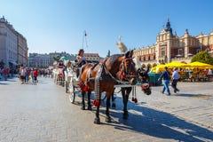 Transportes do cavalo no quadrado principal em Krakow em um dia de verão, Polônia fotos de stock