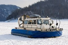 Transporteur d'aéroglisseur sur la glace de la rivière dans le jour d'hiver Photographie stock libre de droits