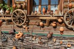 Transportez en charrette les roues et les pots en céramique accrochant sur un mur de maison de village Barrière d'acacia en bas photo stock