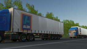 Transportez semi les camions avec le logo d'Aldi conduisant le long du chemin forestier Rendu 3D éditorial Photographie stock libre de droits