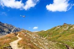 Transportieren Sie Hubschrauberfliegen mit Versorgungen und Bergpanorama mit alpiner Hütte, Alpen Hohe Tauern, Österreich Lizenzfreies Stockfoto