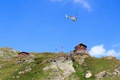 Transportieren Sie Hubschrauberfliegen mit Versorgungen und Bergpanorama mit alpiner Hütte, Alpen Hohe Tauern, Österreich Lizenzfreies Stockbild
