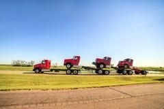 Transportieren von drei neuen roten LKWs Lizenzfreie Stockfotos