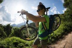 Transportierende Mountainbike des Radfahrers auf Gebirgspfad Stockbilder
