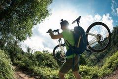 Transportierende Mountainbike des Radfahrers auf Gebirgspfad Lizenzfreie Stockfotos