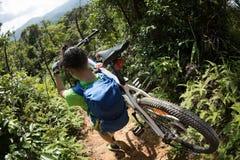 Transportierende Mountainbike des Radfahrers auf Gebirgspfad Lizenzfreies Stockfoto