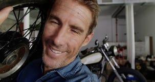 Transportierendes Motorrad des männlichen Mechanikers drehen sich in Reparaturgarage 4k stock footage