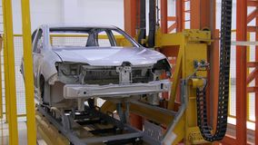 Transporting belt is moving car bodies inside a workshop, putting one down