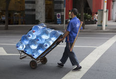 Transporting drink barreled water with cart Stock Images