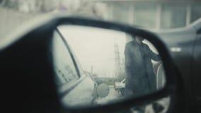 Transportu i posiadania pojęcie - obsługuje pompować benzyny paliwo w samochodzie przy benzynową stacją, widok od lustra, deszczo zdjęcie wideo