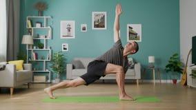 Transportwagen aus dem erwachsenen Mann heraus, der morgens Yoga in seinem Wohnzimmer tut stock video