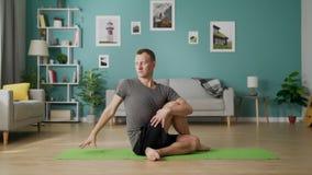 Transportwagen herein des jungen Mannes, der morgens Yoga in seinem Wohnzimmer tut stock video footage