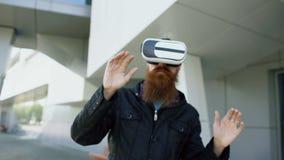 Transportwagenschuß des jungen bärtigen Mannes, der Kopfhörer der virtuellen Realität für 360 VR-Erfahrung und Nehmen von den Glä stock video