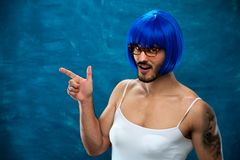 Transsexual person wearing blue wig and glasses. Showing something useful on blank space. Place for text Stock Image