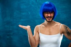 Transsexual person wearing blue wig and glasses. Showing something useful on blank space. Place for text Stock Photo