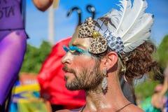 Transsexual z ogromnymi błękitnymi rzęsami, kolczykami, kapitałką z lamparta łękiem i piórkami, Bloco Orquestra Voadora, Carnaval Zdjęcia Stock