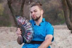 Transsexuellgut aussehender mann mit bilden, das Haarbrötchen, das auf Sand im blauen Kimono sitzt und blinzeln und zeigen das Kü lizenzfreies stockfoto
