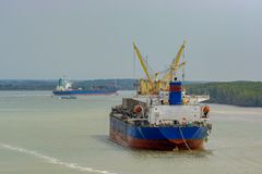 Transshipping operation on vietnamese river. Bulk Carrier vessel performs its dry cargo transshipping operation to the river bulk cargo on Song Long river stock images