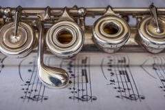 Transversal Flute Detail. Transversal flute instrument detail, over a music sheet Stock Images