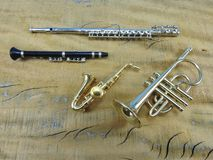 A transverse flute, a clarinet, a saxophone and a trumpet on a wooden surface. royalty free stock photography