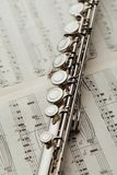 Transverse flute on music sheet. Closeup view Royalty Free Stock Images