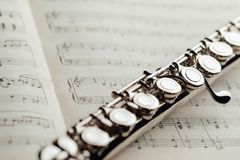 Transverse flute on music sheet. Closeup view Royalty Free Stock Photos