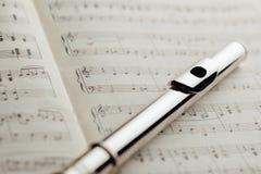 Transverse flute on music sheet Stock Photos