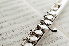 Transverse flute on music sheet. Closeup view Royalty Free Stock Photo