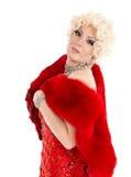 Transvestit i röd klänning med att utföra för päls Arkivfoto