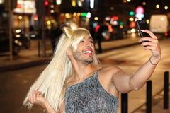 Transvestite taking a selfie outdoors royalty free stock photo
